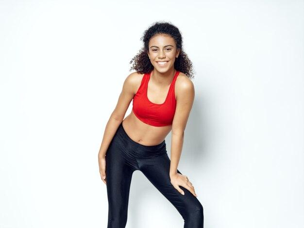 Femme afro-américaine à la peau foncée posant dans un survêtement et faisant de l'espace sportif