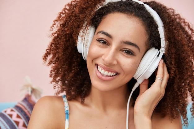 Une femme afro-américaine à la peau foncée positive écoute de la musique populaire en ligne, a un large sourire