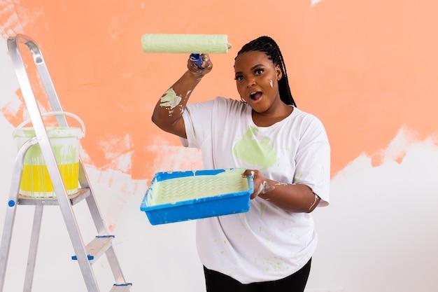 Femme afro-américaine peignant un appartement. concept de rénovation, réparation et redécoration.