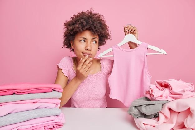 Une femme afro-américaine pensive tient une chemise sur un cintre regarde ailleurs avec une expression réfléchie est assise à table avec des tas de vêtements dépliés isolés sur rose