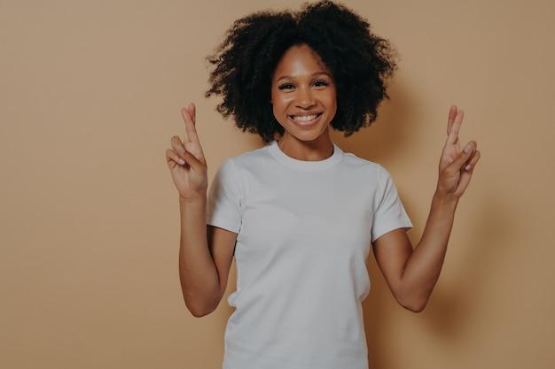 Une femme afro-américaine pleine d'espoir isolée sur fond beige studio croisant les doigts en faisant un vœu