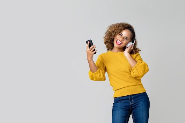 Femme afro-américaine portant des écouteurs en écoutant de la musique