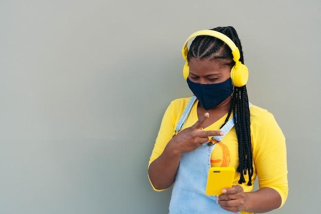 Femme afro-américaine portant un masque de protection et prenant une photo avec son smartphone.