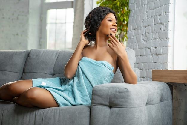 Femme afro-américaine portant une serviette faisant sa routine quotidienne de soins de la peau à la maison.