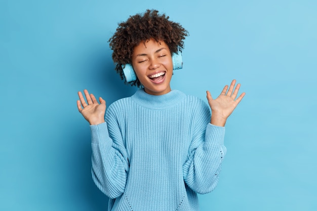 Femme afro-américaine positive aux cheveux bouclés soulève les paumes a du plaisir tout en écoutant la piste audio porte des écouteurs sans fil habillé en cavalier décontracté