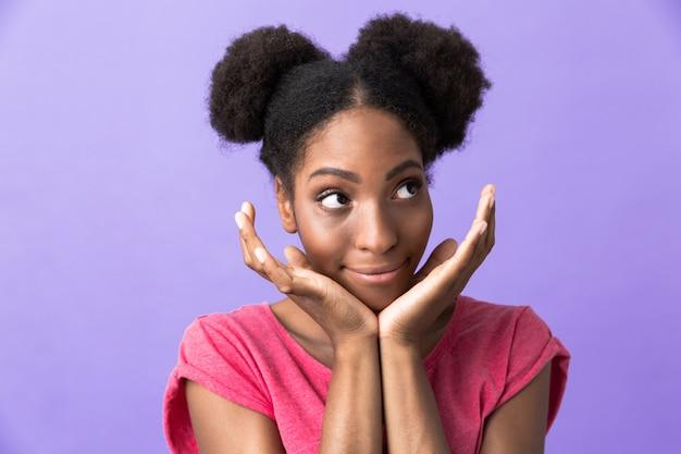 Femme afro-américaine positive souriant et touchant son visage, isolé