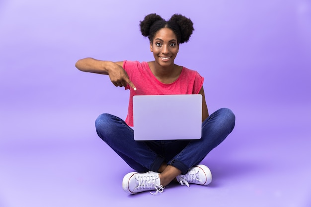 Femme afro-américaine positive souriant et utilisant un ordinateur portable d'argent, alors qu'il était assis sur le sol avec les jambes croisées, isolé