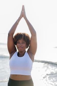 Femme afro-américaine pratiquant le yoga à la plage