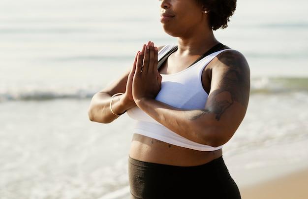 Femme afro-américaine, pratiquer l'yoga à la plage