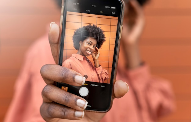 Femme afro-américaine prenant un selfie avec son smartphone
