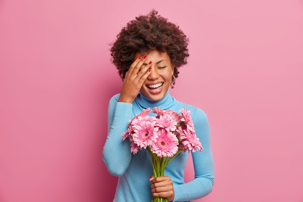 Femme afro-américaine ravie de rire aux éclats, garde la paume sur le visage, se tient à l'intérieur avec un bouquet de fleurs de gerbera