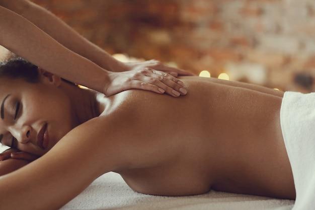 Femme afro-américaine recevant un massage relaxant au spa