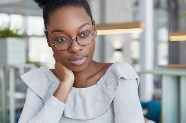 Une femme afro-américaine réfléchie à la peau foncée, a les lèvres charnues, porte des lunettes rondes, est plongée dans ses pensées, rêve d'un bon repos, pense à quelque chose.