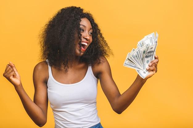 Femme afro-américaine réussie tenant beaucoup de billets en dollars d'argent