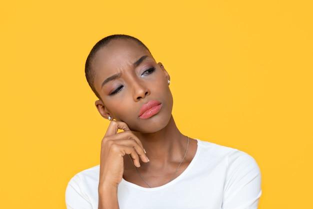 Femme afro-américaine, s'ennuyer sur un mur isolé jaune