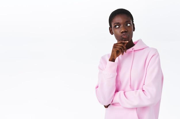 Une femme afro-américaine séduisante et réfléchie aux cheveux courts, portant un sweat à capuche rose élégant, faisant la moue et ayant l'air curieuse, pensant