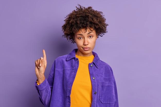 Une femme afro-américaine sérieuse a les cheveux bouclés vous assure d'aller à l'étage indique avec l'index ci-dessus porte des vêtements à la mode.