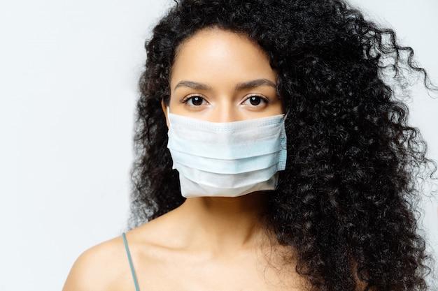 Une femme afro-américaine sérieuse tente d'arrêter le virus et les maladies épidémiques, reste à la maison pendant une épidémie infectieuse, porte un masque médical, isolé sur fond blanc, étant hospitalisée, diagnostiquée