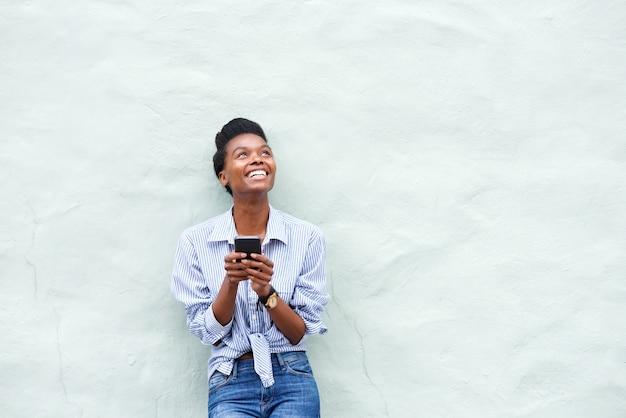 Femme afro-américaine souriant avec téléphone portable et levant les yeux