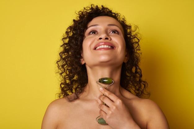 Femme afro-américaine souriante aux cheveux bouclés massant son cou avec un rouleau de jade, isolé