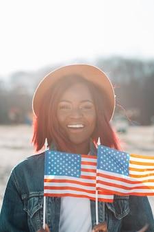 Femme afro-américaine souriante avec des drapeaux américains