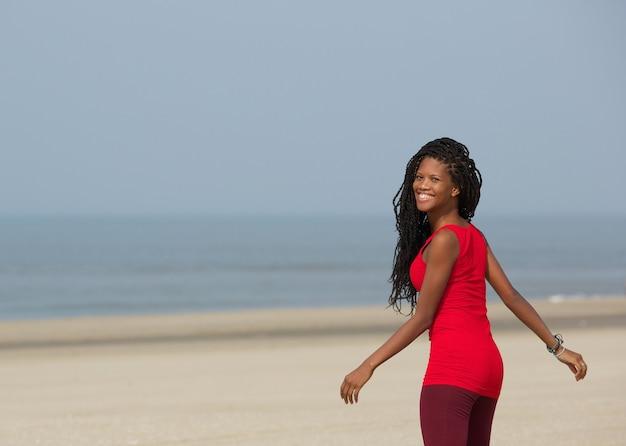 Femme afro-américaine souriante, marchant sur la plage