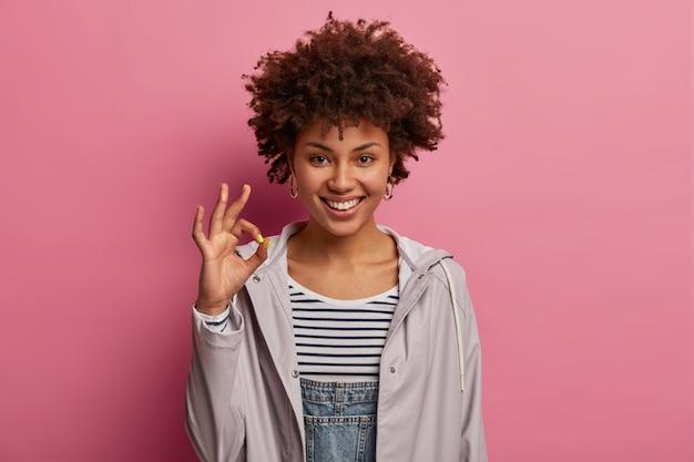 Une femme afro-américaine souriante positive est d'accord avec vous, donne des recommandations et laisse de bons commentaires, a une expression heureuse, suggère quelque chose, porte un anorak gris, pose sur un mur rose