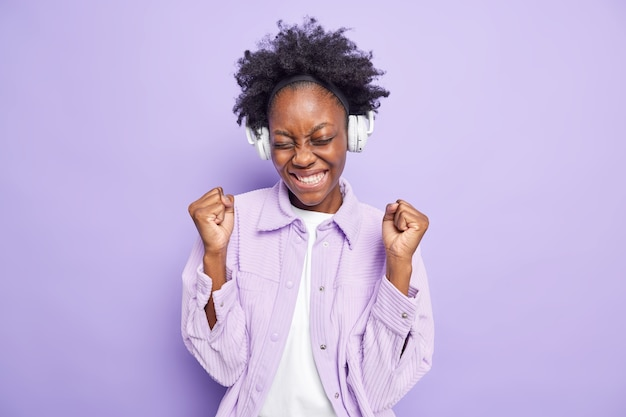 Une femme afro-américaine à succès positif serre les poings de joie écoute une nouvelle liste de lecture de musique via des écouteurs sans fil