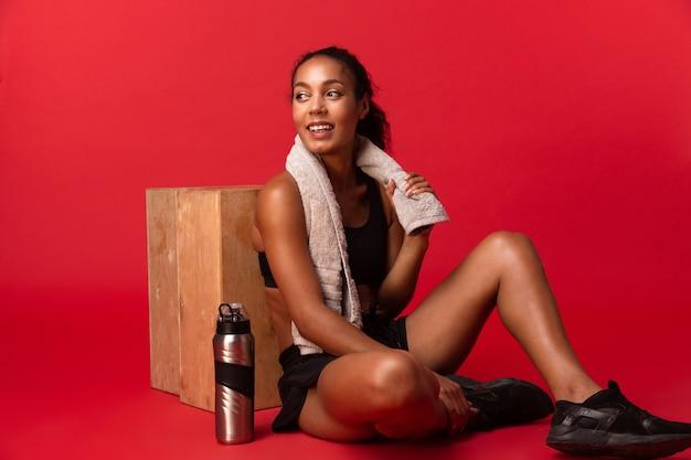 Femme afro-américaine en survêtement noir assis sur le sol avec une serviette et une bouteille d'eau, isolé sur mur rouge