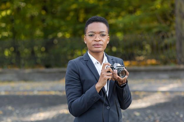 Une femme afro-américaine tenant un appareil photo argentique prend des photos dans le parc et regarde la caméra