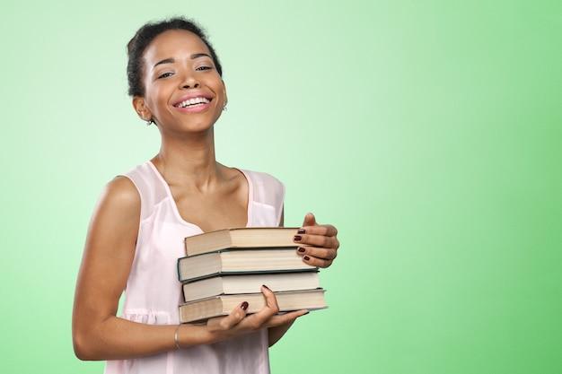 Femme afro-américaine tenant une pile de livres