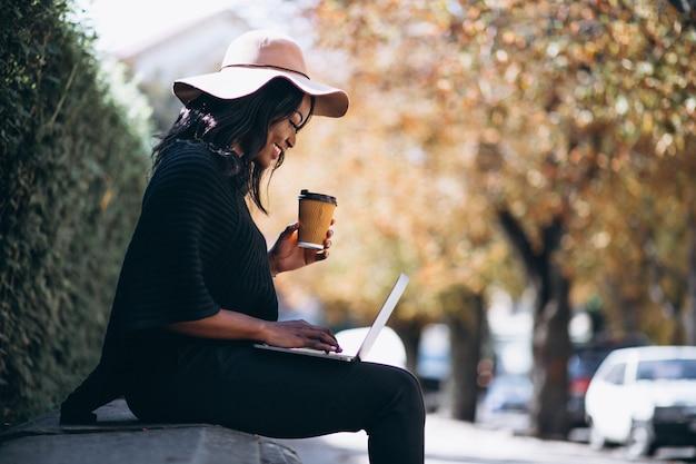 Femme afro-américaine travaillant sur un ordinateur en plein air