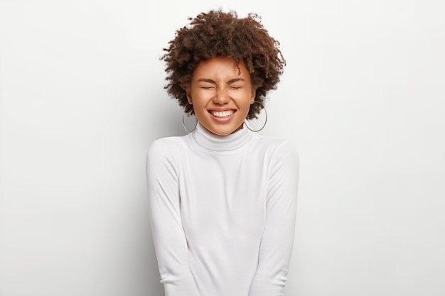 Une femme afro-américaine trop émotive rit positivement, garde les yeux fermés, sourit à une histoire drôle, exprime de bonnes émotions, porte des vêtements blancs, isolée, a une coupe de cheveux bouclée. les gens et les émotions.
