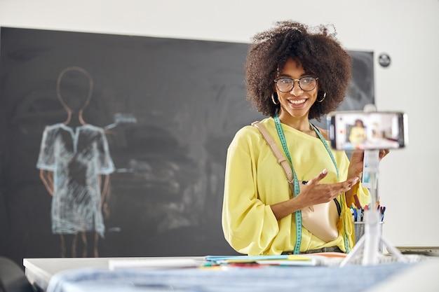 Une femme afro-américaine, une tutrice de cours de conception de vêtements, montre une palette de couleurs à l'appareil photo d'un téléphone portable