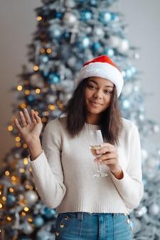 Femme afro-américaine avec verre de champagne à la maison. célébration de noël