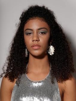 Femme afro-américaine en vêtements de mode festive brillante sur un espace coloré posant