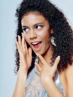 Femme afro-américaine en vêtements de mode festive brillante sur un fond coloré posant