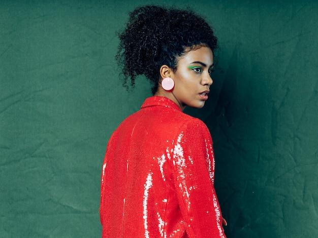 Femme afro-américaine en vêtements de mode festive brillante sur une surface colorée posant