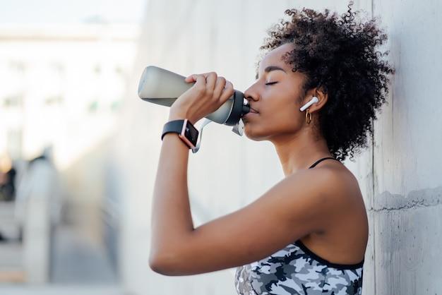 Femme afro athlétique, boire de l'eau et se détendre après un entraînement à l'extérieur.
