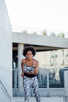 Femme afro athlétique en cours d'exécution et faire de l'exercice à l'extérieur