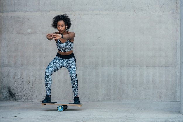 Femme afro athlétique exerçant et faisant la jambe accroupie à l'extérieur. concept de sport et de mode de vie sain.