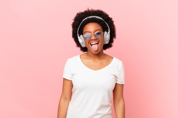 Femme afro avec une attitude joyeuse, insouciante, rebelle, plaisantant et tirant la langue, s'amusant. notion de musique