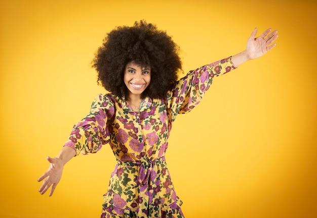 Femme afro câlin heureux, fond jaune