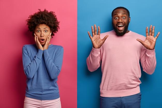 Une femme afro choquée garde les mains sur les joues et regarde la caméra avec surprise