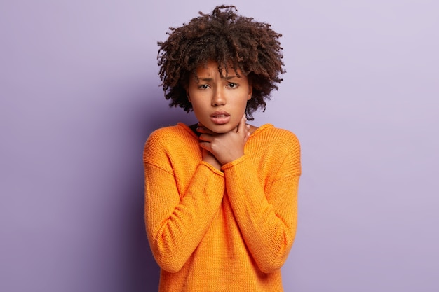 Une femme afro déprimée a un étranglement douloureux dans la gorge, étouffe, souffre d'asthme