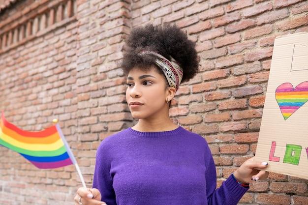 Femme afro avec drapeau de la fierté gay dans la rue