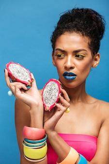 Femme afro fascinante avec des cosmétiques colorés sur le visage à la recherche sur les fruits du dragon juteux coupés en deux tenant dans les deux mains isolées, sur le mur bleu