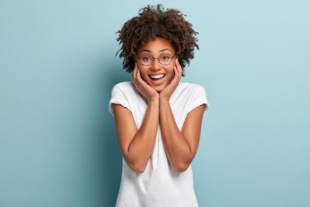 Femme afro insouciante optimiste touche les deux joues, a un large sourire, montre des dents blanches, habillée en tenue décontractée, lunettes rondes