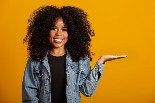 Une femme afro joyeuse pointe du doigt sur l'espace de copie, discute d'une promo incroyable, cède la place ou la direction, porte un pull chaud jaune, a un sourire agréable, se sent optimiste, isolée sur un mur jaune.
