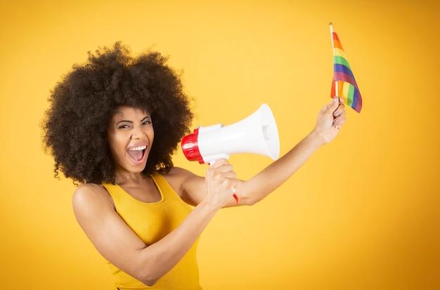Femme afro mixte avec drapeau de la fierté gay et mégaphone, crie pour ses droits, sur fond jaune